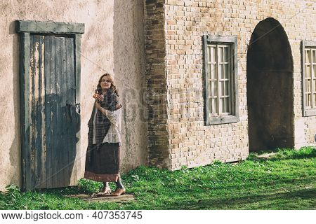 A Woman Stands In Full Growth Against The Background Of An Old Wall In A City Landscape. Brunette Wo