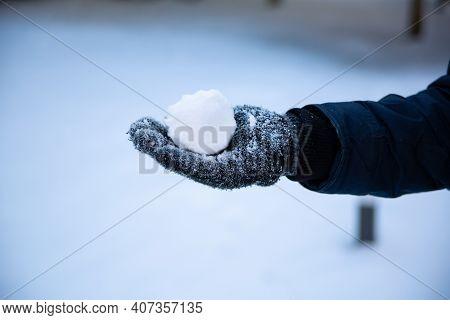 A Snowball In A Hand In A Winter Glove. Winter Fun, Throwing Snowballs, Outdoor Recreation.