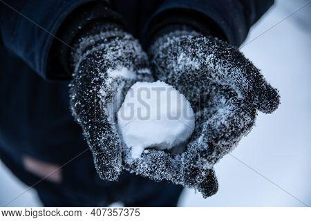 A Snowball In Hands In Winter Gloves. Winter Fun, Throwing Snowballs, Outdoor Recreation.