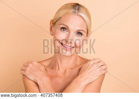 Portrait Of Positive Middle Aged Woman Embrace Herself Enjoy Rejuvenation Skin Isolated Over Beige C