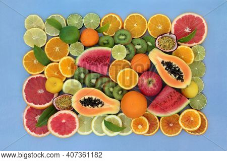 Large collection of high fibre fruit very high in antioxidants, anthocyanins, lycopene and  vitamin c. Immune boosting health care concept. Flat lay top view with border on mottled blue background.