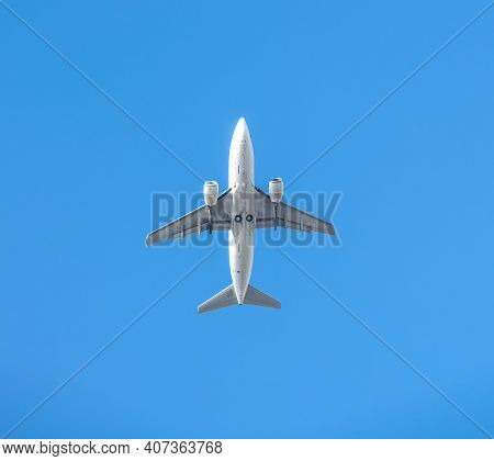 Bottom View Of The White Passenger Plane After Takeoff