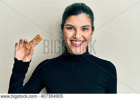 Young hispanic woman eating protein bar as healthy energy snack looking positive and happy standing and smiling with a confident smile showing teeth