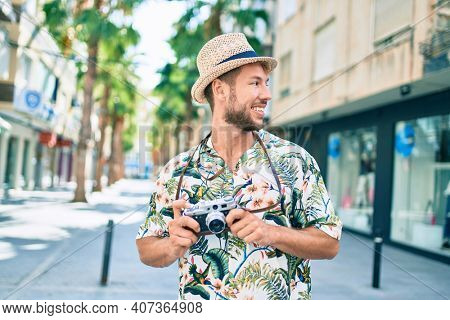 Handsome caucasian man wearing summer hat and flowers shirt smiling happy outdoors taking pictures using vintage camera