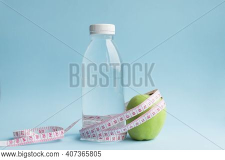 Bottle Of Water, Apple With Measuring Tape On Blue Background. Weight Loss, Counting Calories And He