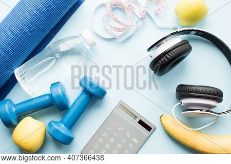 Calculator, Dunbbell, Fruits And Healthy Lifestyle Assesories On Blue Background. Weight Loss, Fitne