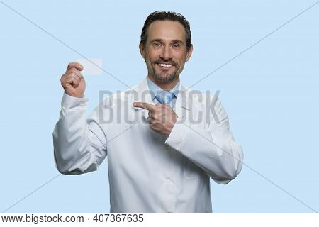 Senior Doctors Pointing At Blank Business Card. Happy Cheerful Mature Physician Advertising His Serv