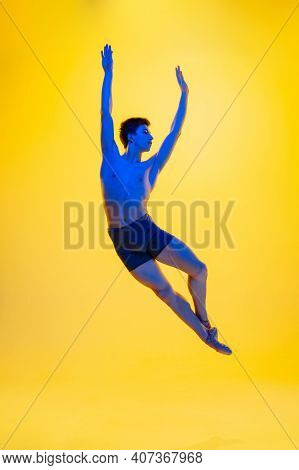 Flying, Jumping. Young And Graceful Ballet Dancer On Yellow Studio Background In Neon Light. Art, Mo