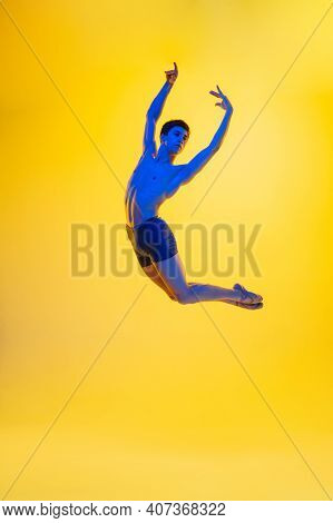 Powerful. Young And Graceful Ballet Dancer On Yellow Studio Background In Neon Light. Art, Motion, A