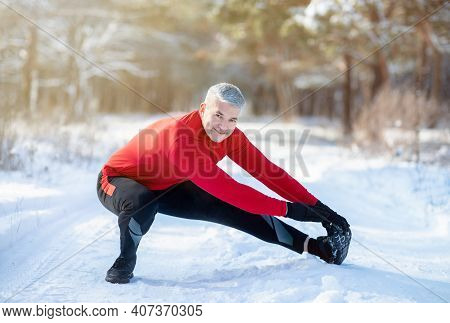 Outdoor Winter Activities Concept. Joyful Senior Man Stretching His Legs Before Jogging At Snowy Par