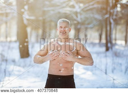 Cold Exposure Training Concept. Joyful Senior Guy Tempering His Body With Snow At Frosty Winter Fore