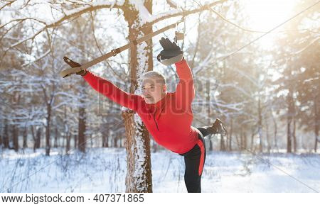 Senior Athletic Man In Sportswear Doing Exercises With Fitness Straps Outdoors On Snowy Winter Day,