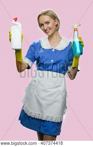 Attractive Housemaid Is Showing Items For Cleaning. Smiling Mature Lady In Apron Isolated On Pink Ba