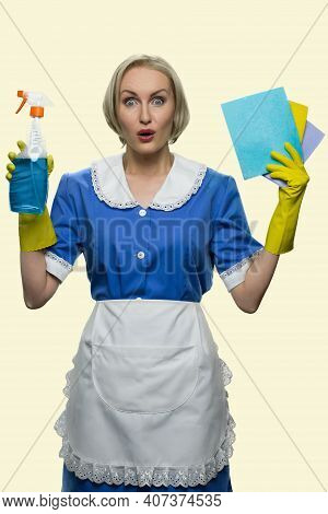 Astonished Housemaid With Rugs And Detergent. Mature European Cleaning Lady With Opened Eyes Isolate