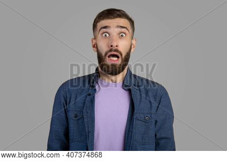 Shocked Bearded Guy Looking At Camera In Panic Over Grey Studio Background. Frightened Young Man Fee