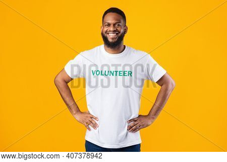Cheerful African Volunteer Guy Standing With His Hands On Hips Ready For Voluntary Work Posing On Ye