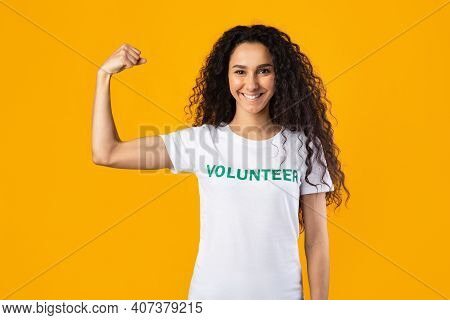 Power Of Kindness. Volunteer Lady Posing Showing Biceps Muscles Standing Over Yellow Studio Backgrou
