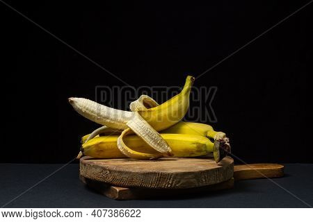 Bananas On A Black Background. Healthy Food. Peeled Banana Lies On Whole Bananas