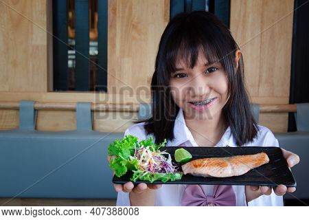 A Girl Teenage Shows A Salted Grilled Salmon In A Japanese Restaurant.