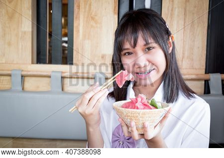 A Girl Teenage Ethnic Asian Shows A Raw Tuna Uses Chopsticks To Pick Up From Tuna Don With Rice And