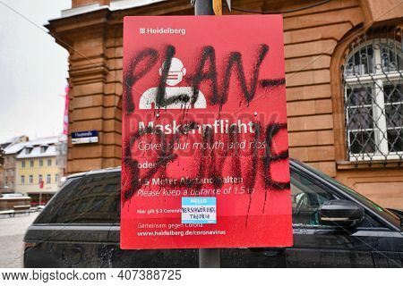 Heidelberg, Germany - February 2021:  Word 'plandemic' In German Written Over Signs For Face Mask An
