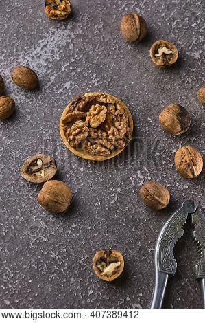 Vintage Walnut Cracker And Walnuts On A Dark Texture Background.