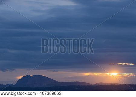 A Panoramic Silhouette Of Hills In The Bottom With Dark Clouds In The Horizon With Sun Peeping Throu