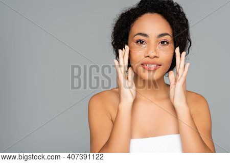 Smiling African American Woman Applying Hydrogel Eye Patches Isolated On Grey.