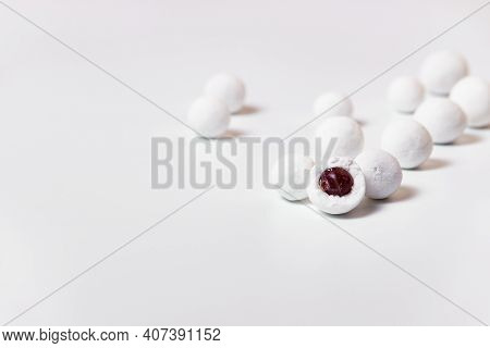 Sweet Balls Of Cranberries In Powdered Sugar Scattered On A White Background.
