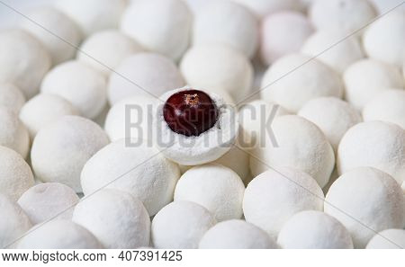 Lots Of White Powdered Sugar Balls With Cranberries In The Center.