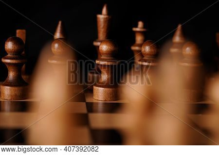 White And Black Wooden Pieces On A Chessboard. A Chessboard Set Up During A Game On A Black Backgrou