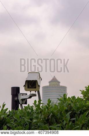 Modern Surveillance Cameras In The Park With Tall Building Background, The Concept Of Surveillance A