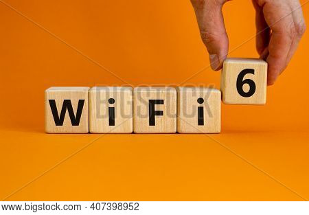 Wifi 6 Symbol. Businessman Holds A Wooden Cube With Words Wifi 6. Beautiful Orange Background, Copy
