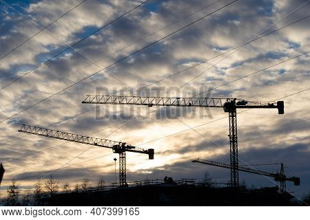 A Large Construction Machine On A Construction Site During The Setting Sun. Stationary Crane Based O
