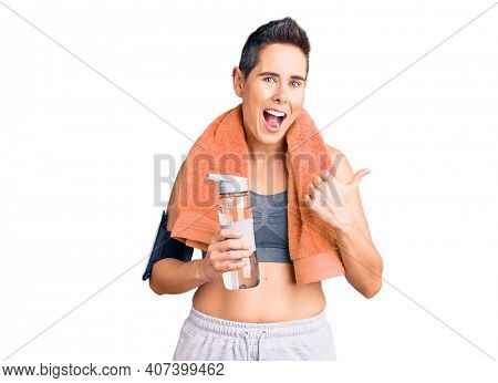 Young woman with short hair wearing sportswear and towel holding bottle of water pointing thumb up to the side smiling happy with open mouth