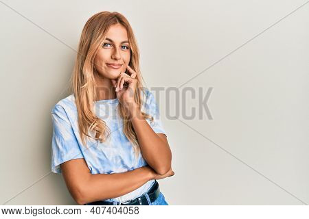 Beautiful blonde young woman wearing tye die tshirt smiling looking confident at the camera with crossed arms and hand on chin. thinking positive.