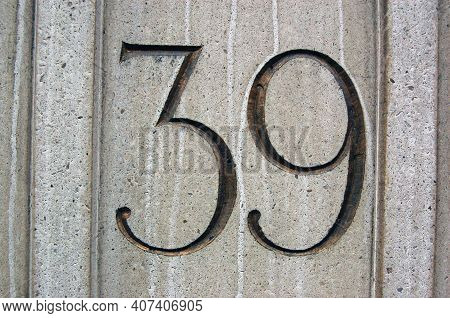 The Number Thirty Nine Carved Into Limestone And Gilded. On The Side Of An Office Building Overlooki
