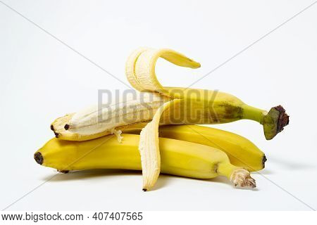 Bananas On A White Background. Fresh Yellow Bananas. A Peeled Banana Lies On Top Of Whole Bananas. E
