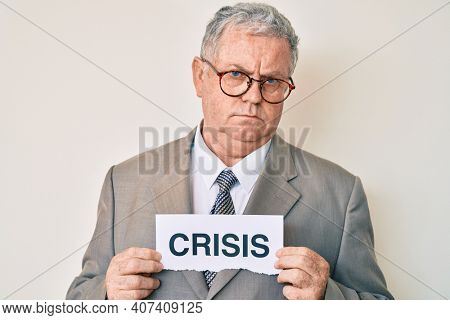 Senior grey-haired man wearing business suit holding crisis paper skeptic and nervous, frowning upset because of problem. negative person.