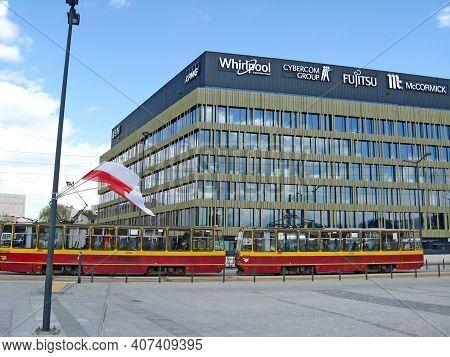 Lodz - Poland. 18 June 2019: Modern Tram Riding Around City. Red Tram Going On City Street In Lodz
