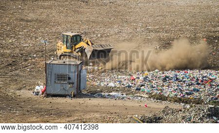 Yellow Tractor Unloading Waste On Huge Landfill Of Big City. A Lot Of Garbage On Dumping Site. Waste