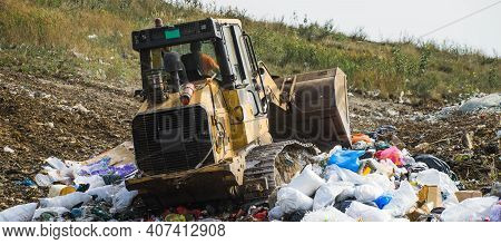 Yellow Tractor On Pile Of Household Garbage. Waste Sorting And Preparation For Recycling On Landfill