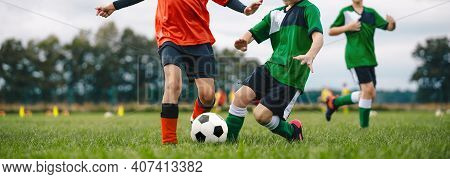 Players Kicking Football Ball On Grass. Young Boys In A Soccer Duel. Group Of School Children Playin