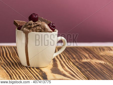 Pudding With Ice Cream, Cherries And Pieces Of Chocolate In A Mug