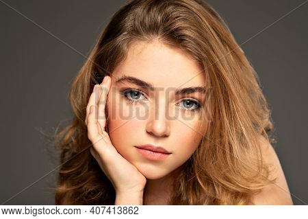 Pretty young woman with long brown hair looking at camera. Closeup portrait of an young adult girl with long curly hair.  Photo of a fashion model posing at studio.  Beauty portrait.