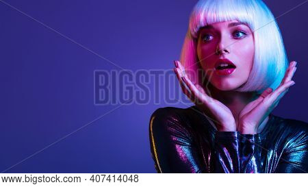 Surprised  Face of glamour girl. Wondered female face in a white wig. Young beautiful woman with a shocked face. Art portrait  of  an young attractive woman with hands at face. Emotional person.