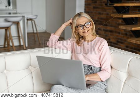 Positive Charming Mature Blonde Woman In Glasses Sitting On The Couch, Resting Relaxing, Thinking Ab