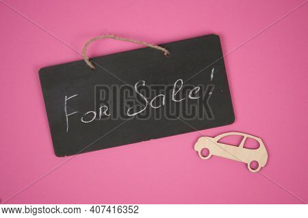 wooden mini toy car with chalkboard on pink background. FOR SALE written on the chalkboard. Conceptual.