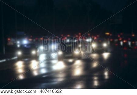 Automobiles With Headlights And Lights On In Night City Blurred. Blur Image With Traffic Jam In City