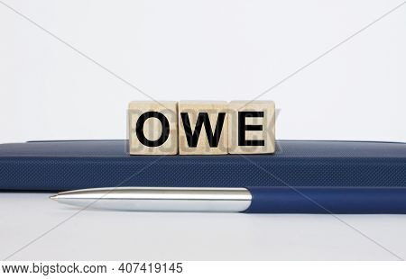 The Text Owe On A Wooden Cubes, Lying On A Notepad With A Metal Blue Pen